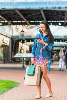 Moça com sacos de compras e telefone celular no mart