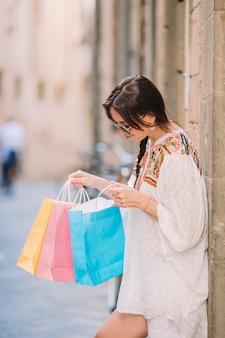 Moça com sacos de compras na rua