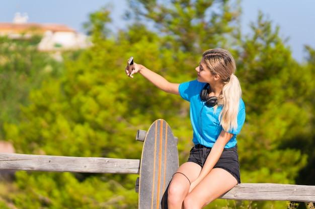 Moça com skate ao ar livre, tomando uma selfie com o celular