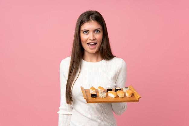 Moça com sushi isolado sobre com surpresa e expressão facial chocada