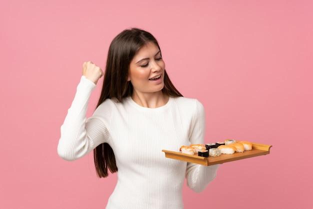 Moça com sushi sobre rosa isolado comemorando uma vitória