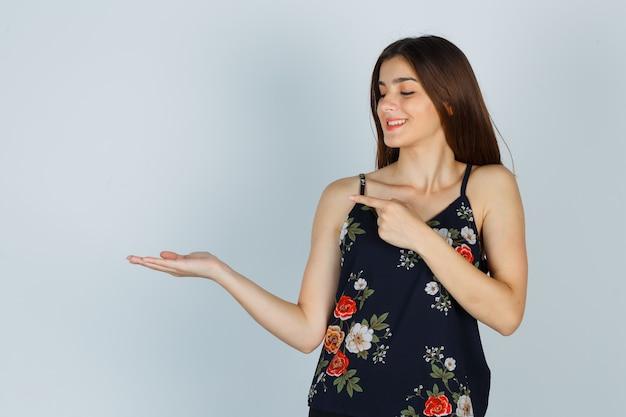 Moça com top floral espalhando palma, apontando para o lado e parecendo satisfeita