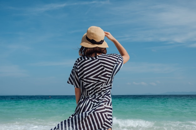 Moça com um chapéu em um vestido listrado na praia. tailândia, ilha de bambu