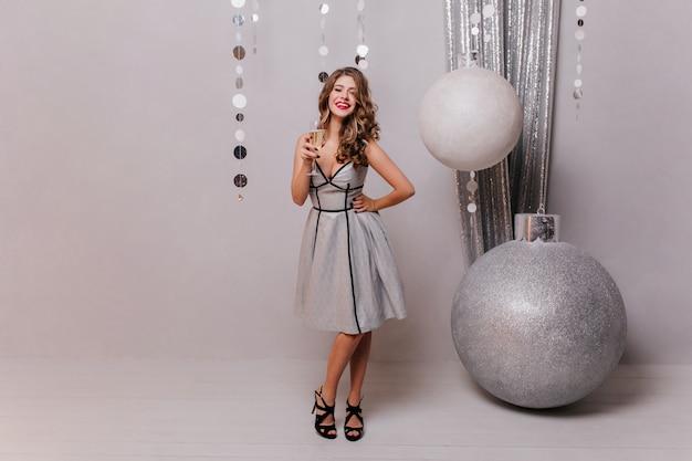 Moça com um lindo vestido de grife e sapatos pretos com salto, posando com uma taça de espumante branco, contra a decoração de natal