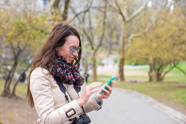 Moça com um telefone no parque
