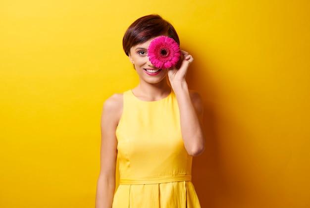 Moça com uma flor na frente do olho