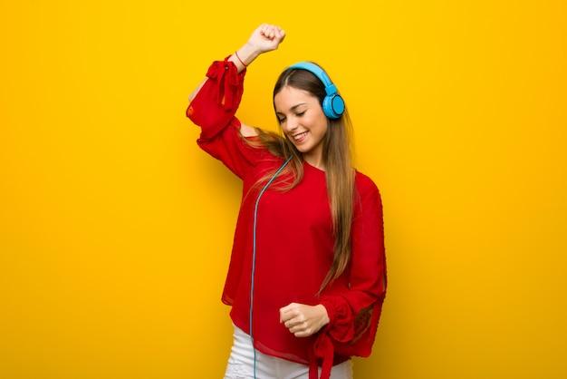 Moça com vestido vermelho na parede amarela, ouvindo música com fones de ouvido e dançando