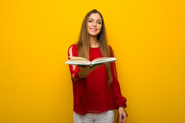 Moça com vestido vermelho na parede amarela, segurando um livro e dando a alguém