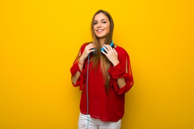 Moça com vestido vermelho sobre parede amarela com fones de ouvido