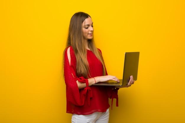 Moça com vestido vermelho sobre parede amarela com laptop