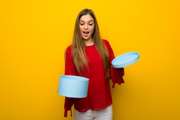 Moça com vestido vermelho sobre parede amarela, segurando a caixa de presente nas mãos