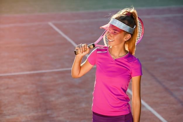 Moça considerável no tampão à moda e sportswear com raquete no ombro no fundo da luz do sol. jogadora de tênis na quadra ao ar livre no ocaso.