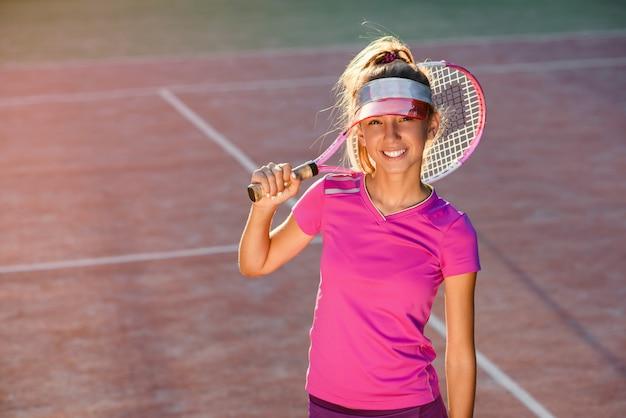 Moça considerável no tampão à moda e sportswear que olha a câmera e que sorri no fundo da luz do sol. jogadora de tênis na quadra ao ar livre no ocaso.