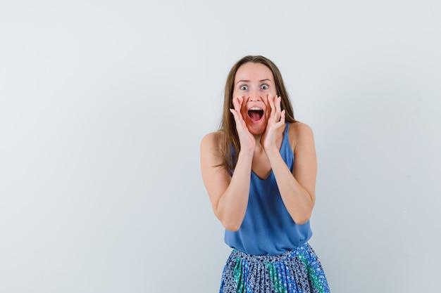 Moça contando segredo ou gritando na camiseta, saia e parecendo animada, vista frontal.