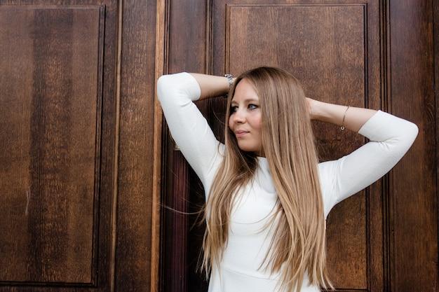 Moça da aparência europeia em um vestido branco no fundo do edifício.