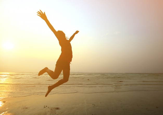 Moça da silhueta que salta com mãos acima na praia no por do sol, borrão de movimento