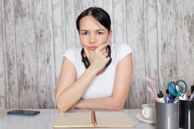 Moça de camisa branca, mostrando emoções com as mãos em fones de ouvido pretos na parede cinza