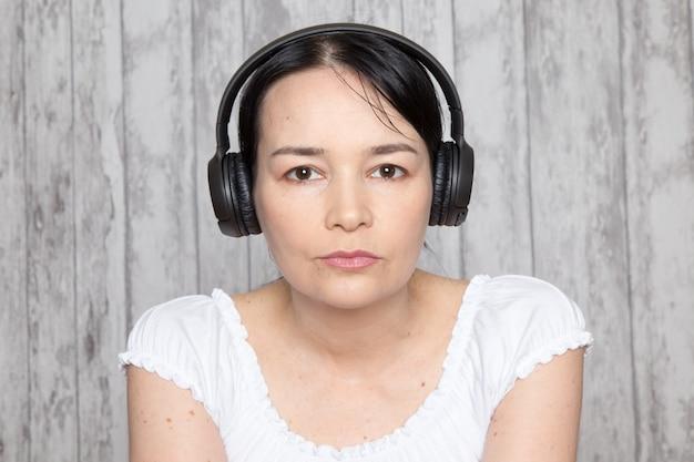 Moça de camisa branca, ouvindo música em fones de ouvido pretos na parede cinza
