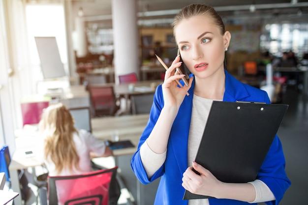 Moça de casaco azul está segurando um tablet plástico e falando ao telefone. ela está conversando com os clientes. mulher parece séria e concentrada.