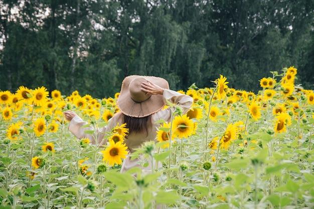 Moça de chapéu em um campo de girassóis