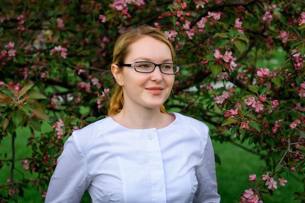 Moça de óculos elegantes no fundo da árvore de florescência