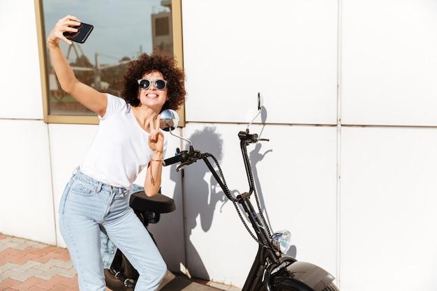 Moça de sorriso nos óculos de sol que toma um selfie