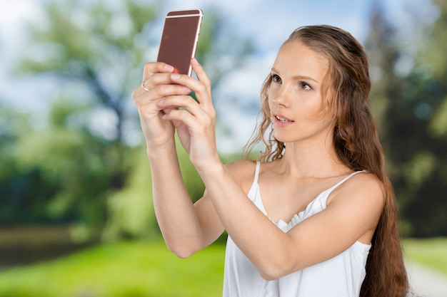 Moça de sorriso que faz a foto do selfie no smartphone