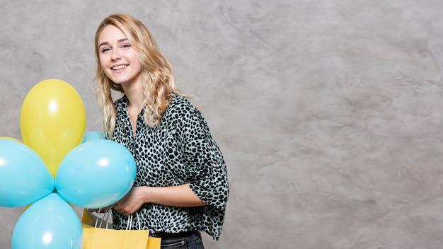Moça de sorriso que guarda balões