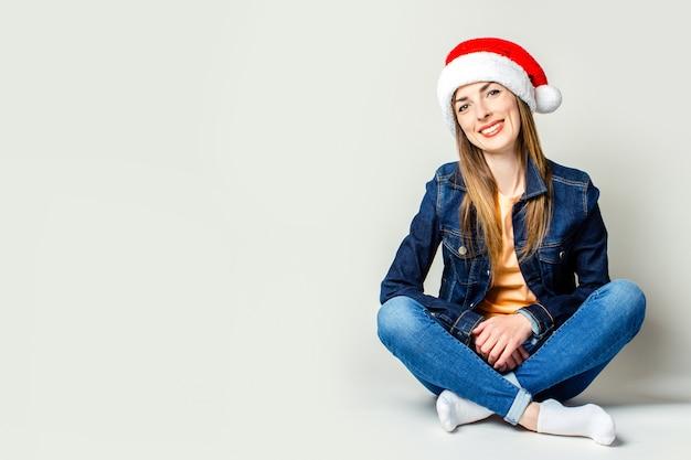 Moça de sorriso que veste um chapéu de papai noel em uma luz de fundo