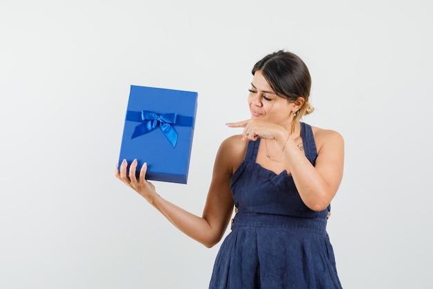 Moça de vestido apontando para a caixa de presente