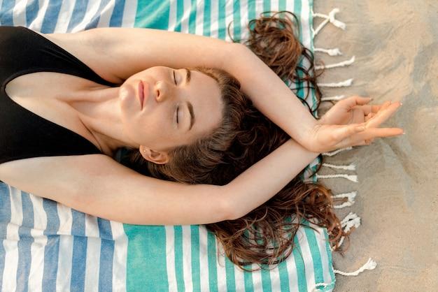 Moça deitada em uma praia