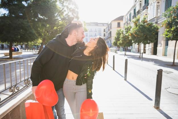 Moça e cara sorridente com pacotes e balões se divertindo na rua