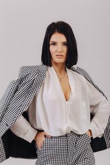 Moça elegante atraente em roupas de negócios posando na parede de luz no estúdio. conceito de roupas elegantes e sofisticação.
