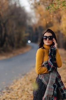 Moça elegante e confortável caminhar no parque outono colorido em óculos de sol