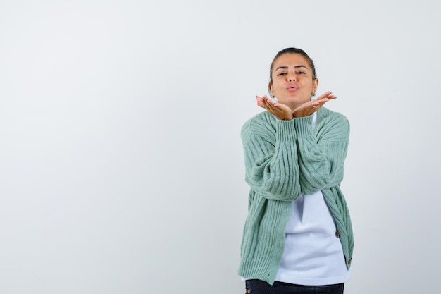 Moça em camiseta, jaqueta mandando beijo com a mão e parecendo fofa