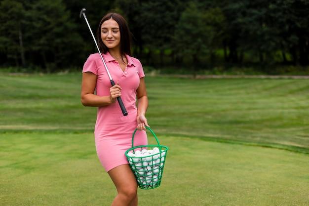 Moça em camiseta rosa no campo de golfe