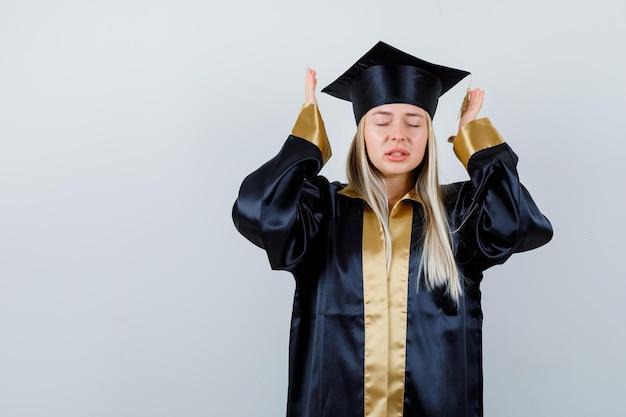 Moça em traje acadêmico, mantendo as mãos de maneira agressiva e parecendo esquecida