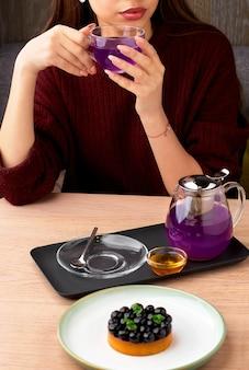 Moça em um restaurante em uma mesa com bolo de mirtilo e chá azul tailandês servido com bolo de mel e mirtilo na mesa de madeira
