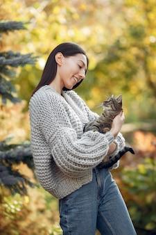 Moça em um suéter cinza posando ao ar livre com um gato