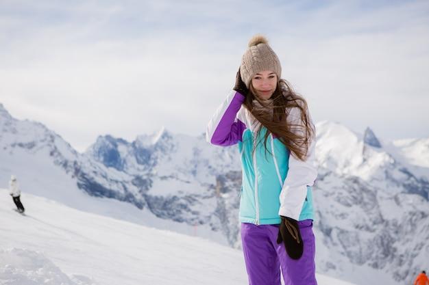 Moça em um terno de inverno que sorri nas montanhas