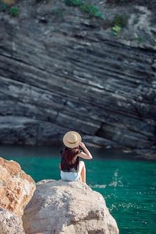 Moça em uma angra em uma rocha na reserva de cinque terre.