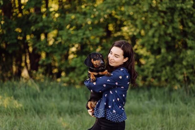 Moça em uma caminhada com seu filhote de cachorro
