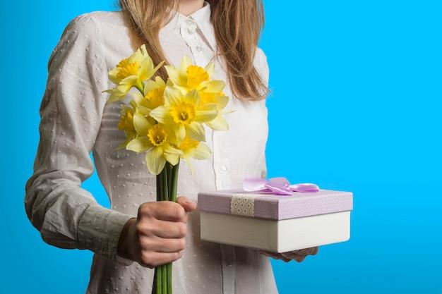 Moça em uma camisa branca está segurando um buquê de flores