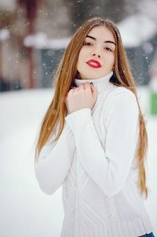 Moça em uma camisola branca que está em um parque do inverno