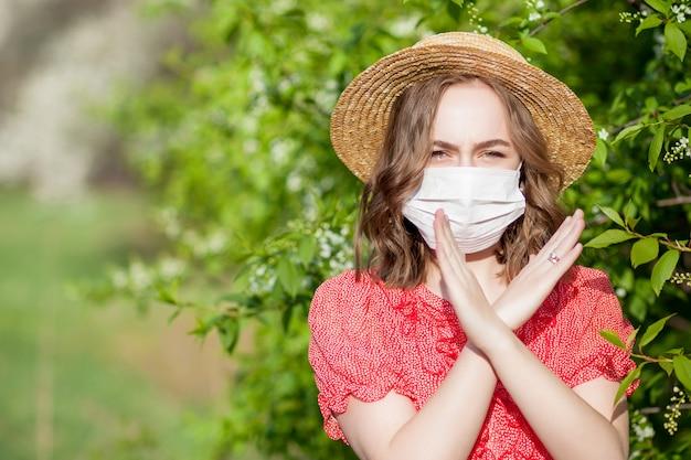 Moça em uma máscara na frente da árvore de florescência. alérgenos sazonais que afetam as pessoas. bela dama tem rinite.