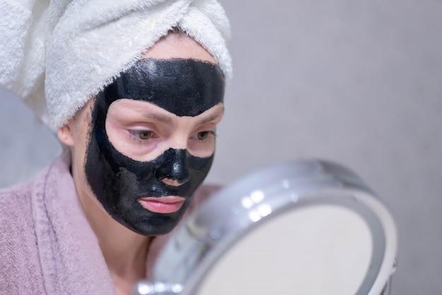 Moça em uma máscara preta de limpeza do carvão em sua cara.