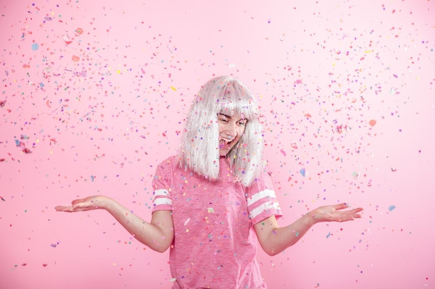 Moça engraçada com cabelo prateado dá um sorriso e emoção no fundo rosa com confete.