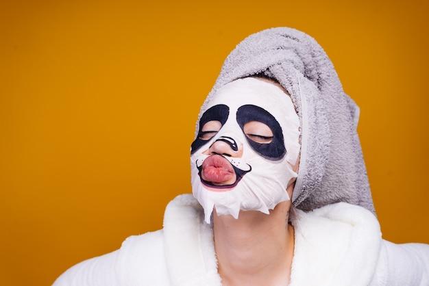 Moça engraçada com uma toalha na cabeça, máscara facial com rosto de animal