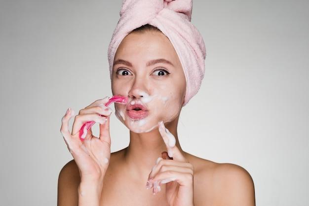 Moça engraçada com uma toalha rosa na cabeça, raspando o rosto como um homem