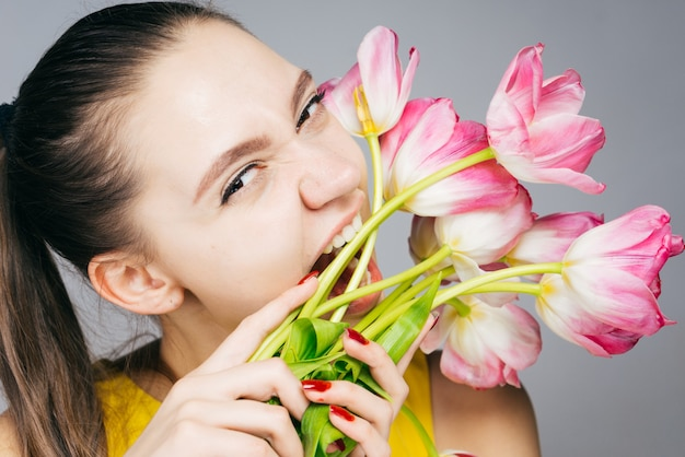 Moça engraçada de vestido amarelo segura flores cor-de-rosa e as morde